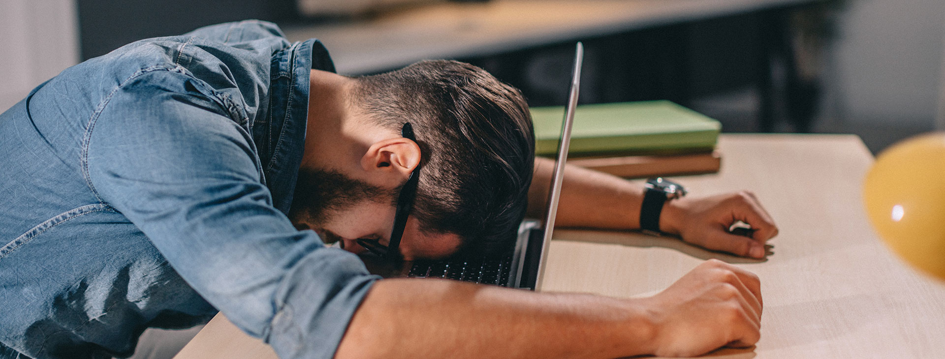 Man slumped over laptop as job sucks