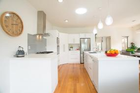Large Open Plan White Kitchen with Feature Wooden Floor